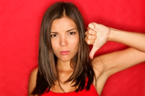 Unhappy woman giving thumbs down gesture looking with negative expression and disapproval. Beautiful cute young mixed race Caucasian / Asian woman on red background.
